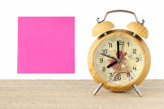 Blank note paper and vintage wooden alarm clock on table Royalty Free Stock Photos