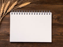 Blank note paper and wheat stalks on wooden background. Top view of blank note paper with wheat stalks on dark brown wood table for background Stock Photo