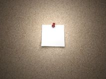 Blank note pinned on a cork board. Blank note pinned down on a cork board with a red pin Royalty Free Stock Photography