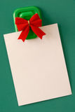 Blank Note With Red Bow. Blank white note paper hanging from magnetic pinup on green background Stock Photography