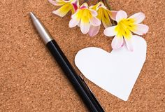 Blank note in shape of heart with copy-sapce and flowers. Blank note in shape of heart with copy-sapce and flowers, on cork surface Royalty Free Stock Photos
