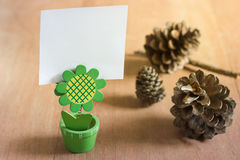 Blank note stand. Small stand with blank white card and dry pine flower on wood background royalty free stock image