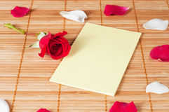 Blank note on a wooden background with a rose and petals Royalty Free Stock Photos