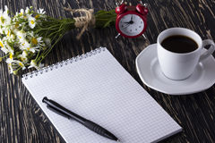 Blank notebook, alarm clock, charmomile and coffee cup. Blank notebook, alarm clock, charmomile and coffee cup on wooden background Stock Photo