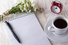 Blank notebook, alarm clock, charmomile and coffee cup. Blank notebook, alarm clock, charmomile and coffee cup on wooden background Stock Photography