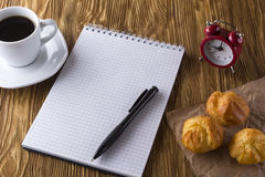 Blank notebook, alarm clock,eclairs and coffee cup. Blank notebook, alarm clock, eclairs and coffee cup on wooden background Stock Photos