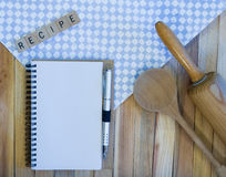 Blank Notebook Awaiting New Recipe. Blank spiral notebook, wooden spoon, rolling pin, pen, recipe on wood background with light blue check napkin Royalty Free Stock Photo
