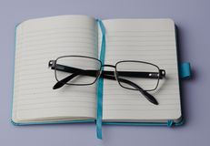Blank notebook with black glasses. Blank light blue notebook with bookmark and with black glasses. Lined paper. On a white background Royalty Free Stock Photo