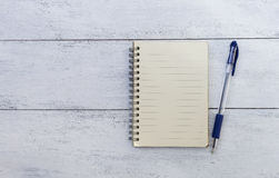 Blank notebook and blue pen on white wood texture. Background Stock Photo
