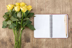 Blank notebook and bunch of yellow roses. On the wooden table Stock Photography