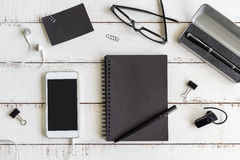 Blank notebook with cellphone on desk office Royalty Free Stock Image