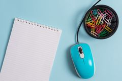 Blank notebook and clips with computer tool placed above pastel backdrop. Paper plus stationary also mouse stick to. Blank notebook and clips with computer mouse royalty free stock photo