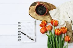 Blank Notebook and Coffee. Overhead shot a blank notebook with pen, coffee and a bouquet of orange and yellow tulips over a wood table. Flat lay top view style Royalty Free Stock Photography