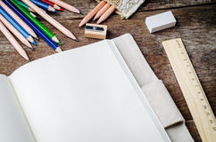 Blank daily notebook with color pencils,  pencil sharpener, rule Stock Image