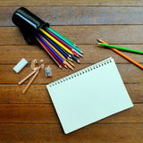 Blank notebook with colored pencils. On wood table Royalty Free Stock Photography