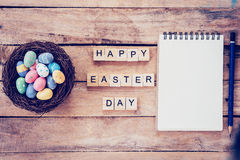 Blank notebook, Colorful easter egg in the nest and wood text for Happy Easter Day on wood background with space royalty free stock photography