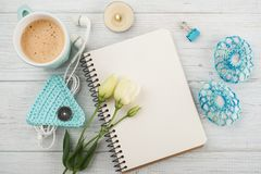 Blank notebooks, gift with green ribbon. Blank notebook, crochet paperweight, earphones, lit candle, flowers on wooden background. Cup of coffee Royalty Free Stock Photo