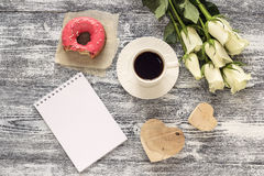 Blank notebook, cup of coffee, donut, hearts and white roses on Stock Image