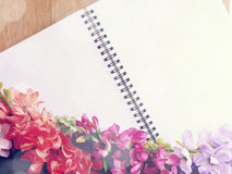 Blank notebook diary with pink flower on wooden background made with vintage filters color Royalty Free Stock Photography