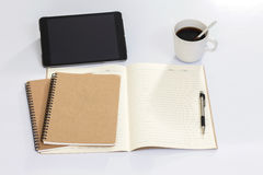 Blank notebook with digital tablet and coffee cup. On white table Stock Photos