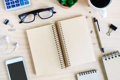 Blank notebook with earphone and a cup of coffee on wooden desk Stock Image