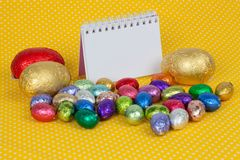 Blank notebook with Easter chocolate eggs. Stock Photo