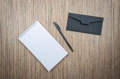 Blank notebook, envelope and pen on wooden background, Mockup stock photography