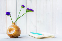 Blank notebook with flower on white wooden table Royalty Free Stock Image