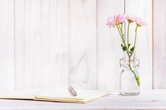 Blank notebook with flower on white wooden table Royalty Free Stock Photography