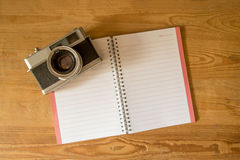 Blank notebook with fountain pen and retro camera on wooden tabl Stock Photos
