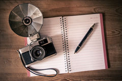Blank notebook with fountain pen and retro camera on wooden tabl Royalty Free Stock Photos