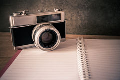 Blank notebook with fountain pen and retro camera on wooden tabl Stock Image