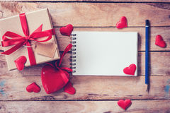 Blank notebook and gift box with red heart on wood background. Stock Photos