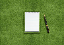 Blank notebook on grass. Blank opened notebook outdoors on the green grassland and pen Stock Photography