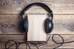 Blank notebook with a headphones on it on wooden background. royalty free stock image