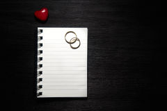 Blank notebook with heart and wedding rings on black background Stock Images