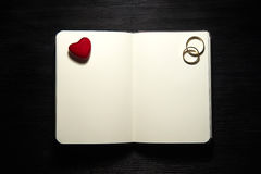Blank notebook with heart and wedding rings on black background Royalty Free Stock Photo
