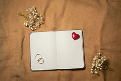 Blank notebook with heart and wedding rings. Royalty Free Stock Photo