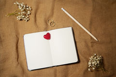 Blank notebook with heart and wedding rings. Royalty Free Stock Photography