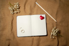 Blank notebook with heart and wedding rings. Royalty Free Stock Images