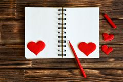A blank notebook with hearts and a red felt-tip pen on a wooden background. Preparation for congratulations on Valentines Day. stock photos