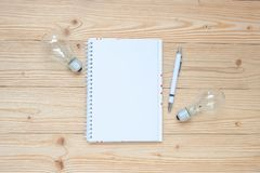 Blank notebook with lightbulb and crumbled paper on wooden table, Top view and copy space. Idea, Creative, Innovation, Solution, S. Trategy, Goals and Mission stock photo