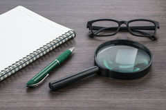 Blank notebook with Magnifier on the deskr, close up Royalty Free Stock Photography