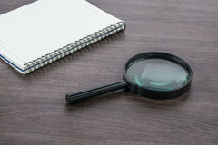 Blank notebook with Magnifier on the deskr, close up Royalty Free Stock Image
