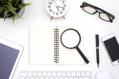 Blank notebook with magnifying glass. Pen, eye glasses, alarm clock, mobile phone, mouse, keyboard, tablet and small plant on white desk background Royalty Free Stock Photography