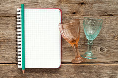 Blank notebook for menu or cocktail recipes. Two wine glasses and blank notebook for menu or cocktail recipes Stock Photos