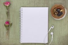 Blank notebook mock up for artwork with pink roses. Place for text. Fresh flowers ans white headphones. royalty free stock photography