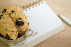 Blank notebook and oat cookies on wood background Stock Images
