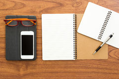 Blank notebook and office accessories on wood table. Background Stock Image