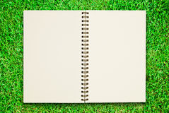 Blank notebook open on green grass field Stock Photography